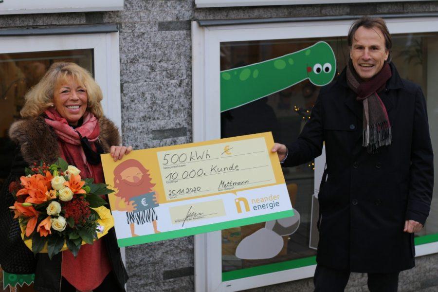 Christa Eichhorn freut sich über Blumen und 500 Kilowattstunden Strom, überreicht von Geschäftsführer Gregor Jeken. Foto: Volkmann