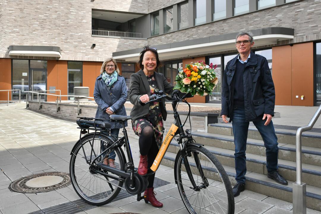 Michael Scheidtmann, Geschäftsführer der Neander Energie, und seine Assistenin, Adrianna Kahle (l.), haben das neue E-Bike und einen Blumenstrauß an Pro Mobil-Geschäftsführerin Margit Benemann übergeben. Foto: Mathias Kehren
