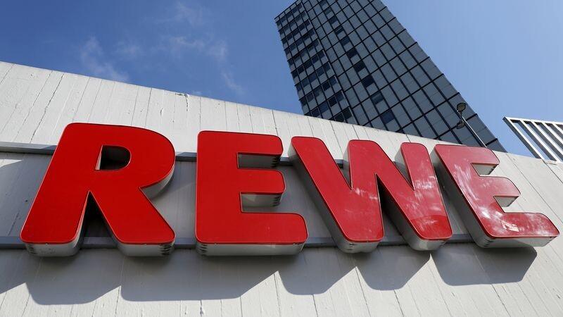Ein Rewe Schriftzug hängt vor einem Supermarkt. Foto: Oliver Berg/dpa/Symbolbild