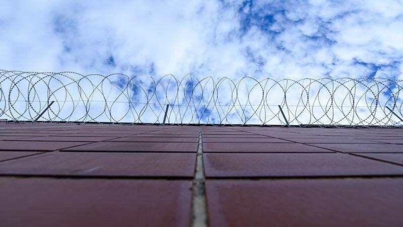 Stacheldrahtzaun hängt an einer Mauer in einer Justizvollzugsanstalt. Foto: Silas Stein/dpa/Symbolbild