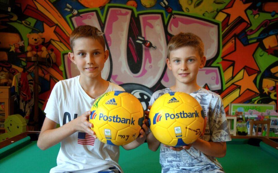Gabriel (links) und Nick zeigen die Hauptpreise, beide handsigniert von Fußball-Legende Franz Beckenbauer. Foto: Stadt Ratingen