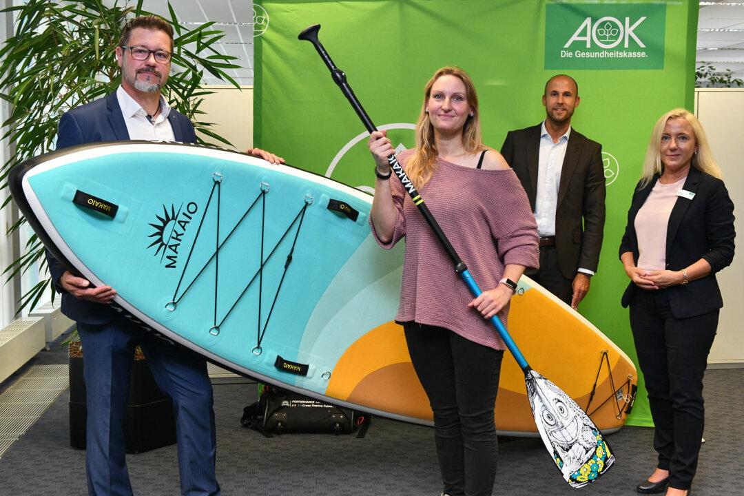 Die AOK Mitarbeiter Thorsten Meier, Christian Cierlitzki und Stefanie Betzer fruen sich mit der glücklichen Gewinnerin, Jennifer Seidel. Foto: Mathias Kehren
